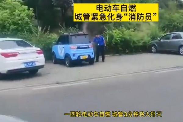 路边停驻的一辆四轮电动车飘出淡淡白烟 执法人员带着车载灭火器冲了上去